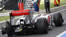 Sergio Perez (MEX) McLaren MP4-28 returns to the pits with a rear tyre puncture in the third practice session.